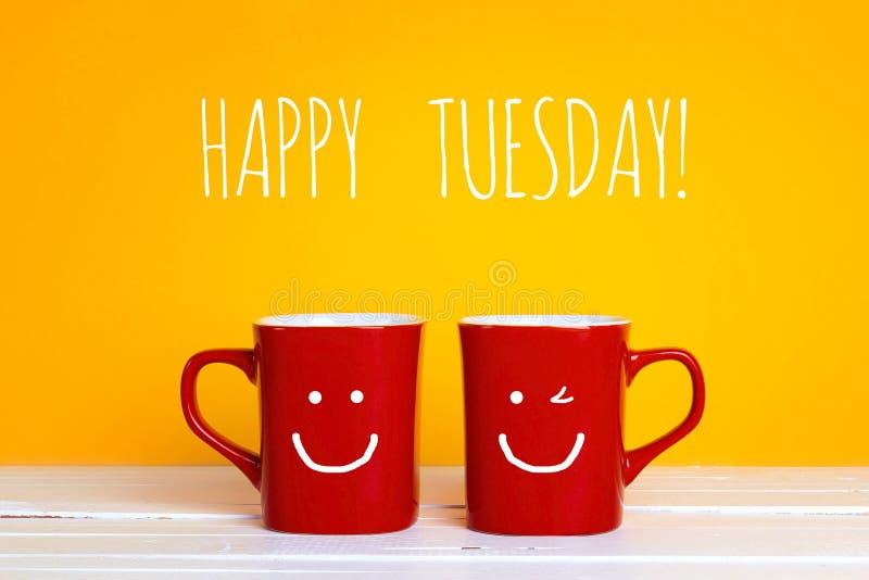 Duas canecas de café vermelhas com caras de sorriso em um fundo amarelo imagens de stock royalty free