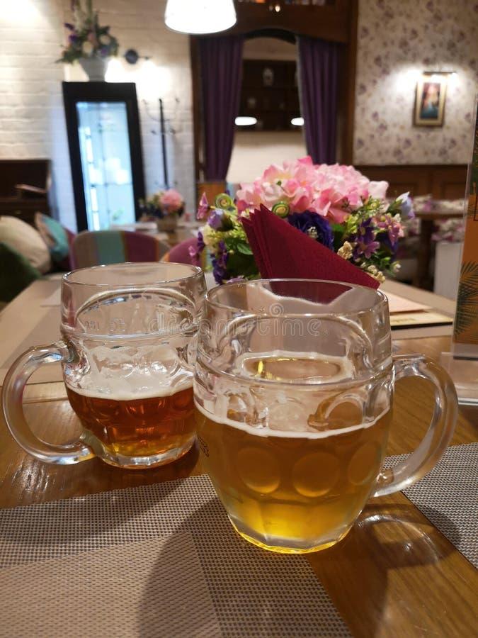 Duas canecas de cerveja que estão na tabela escura e clara no fundo do interior bonito do café imagens de stock