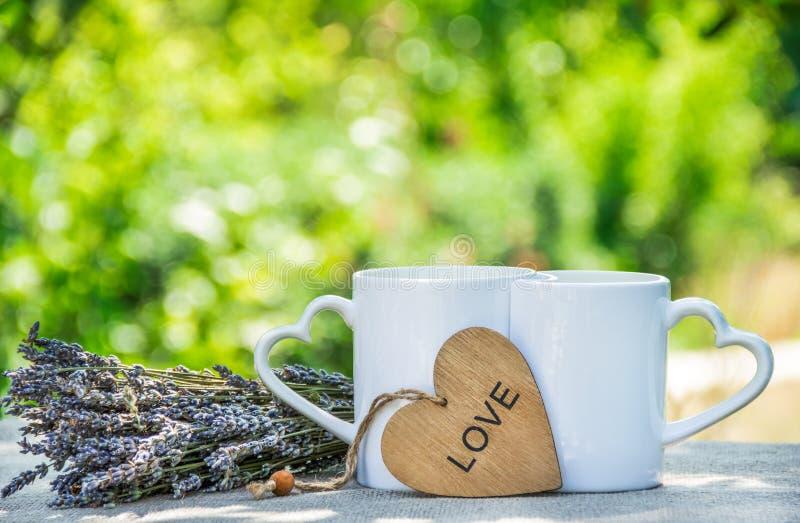 Duas canecas de chá no jardim Café romântico da manhã Caneca com um coração imagem de stock royalty free
