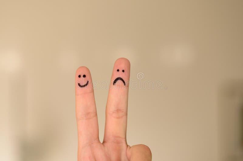 Duas caras tiradas mão do emoticon no dedos das pessoas imagens de stock