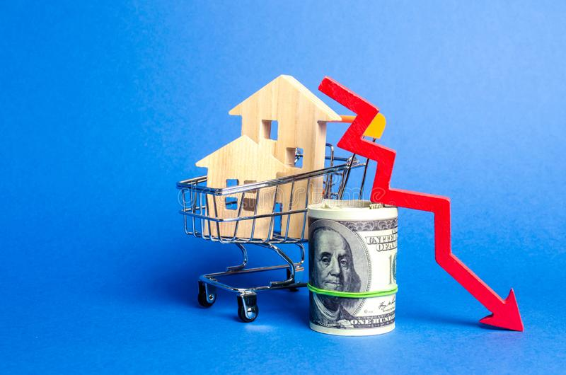 Duas casas de madeira em um carro de troca e em uma seta vermelha para baixo mercado imobiliário de queda Interesse reduzido na h imagem de stock