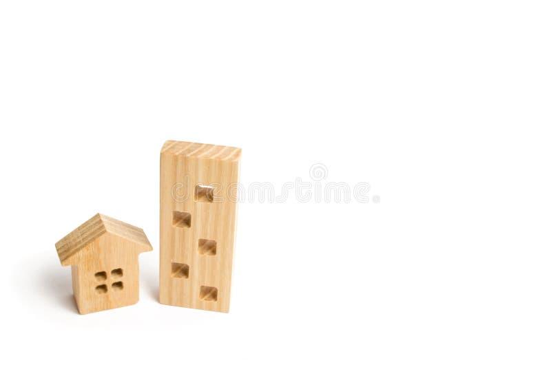 Duas casas de madeira em um fundo branco Uma grande casa melhor então pequena O conceito de comprar uma casa ou um apartamento pr foto de stock