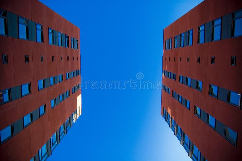 Duas casas na frente de se Tomada da foto do baixo ângulo; duas construções suburbanas vermelhas que enfrentam-se com o céu azul  imagens de stock royalty free