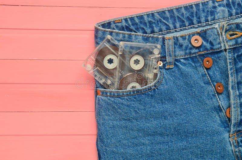 Duas cassetes áudio no calças de brim pocket em uma superfície de madeira cor-de-rosa Tecnologia dos meios dos anos 80 foto de stock
