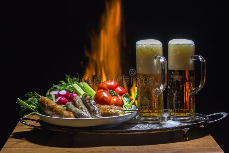Duas cervejas e salsichas com a chama no fundo imagem de stock royalty free