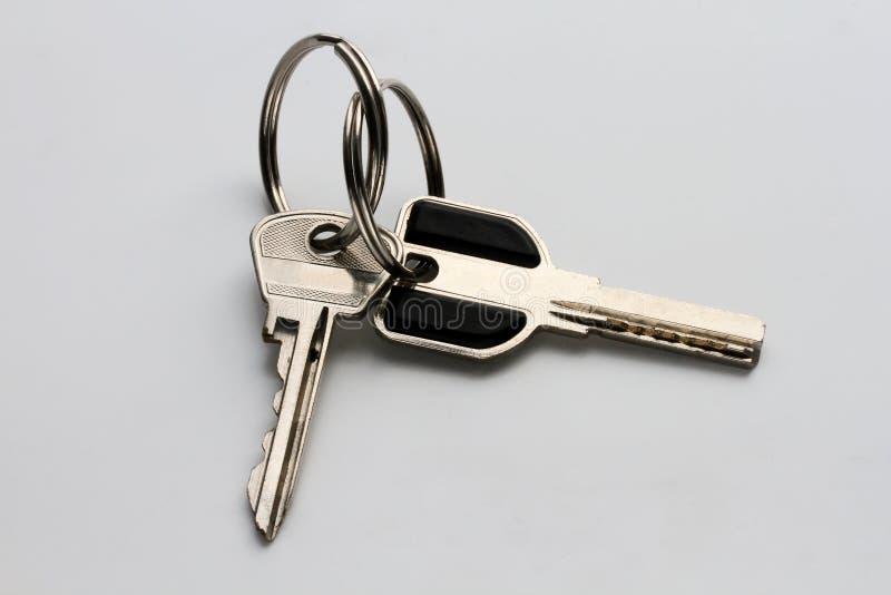 duas chaves do metal em um fundo cinzento homogêneo imagem de stock