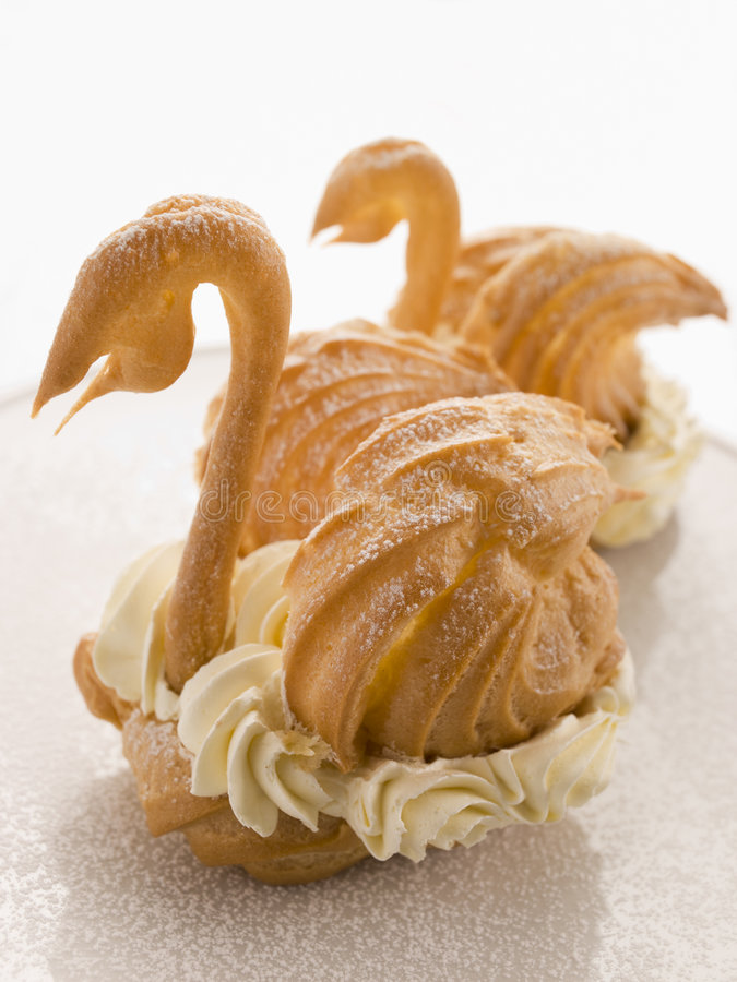 Duas cisnes dos Choux enchidas com o creme de Chantilly fotos de stock royalty free