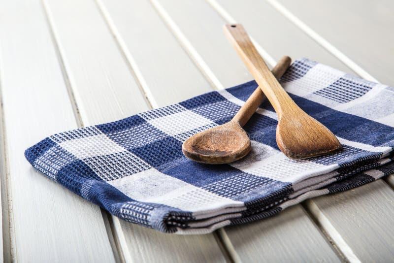Duas colheres de cozimento de madeira na toalha azul na tabela de madeira foto de stock