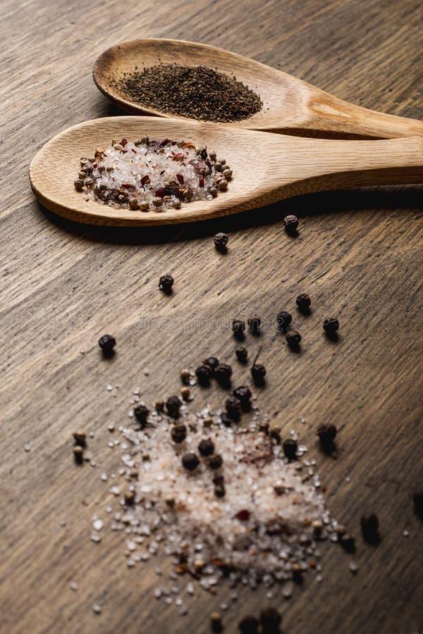 Duas colheres de madeira com sal e pimenta em uma tabela de madeira imagens de stock