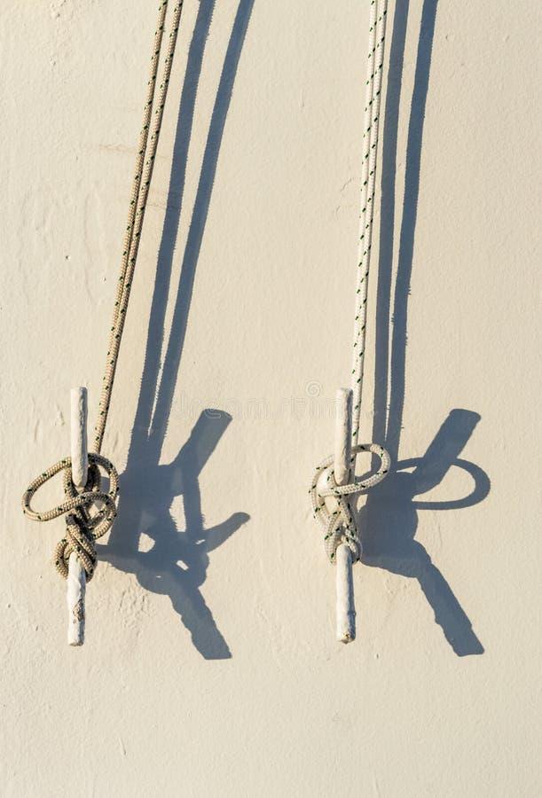 Duas cordas náuticas amarradas aos grampos do metal na parede do navio de cruzeiros fotografia de stock royalty free