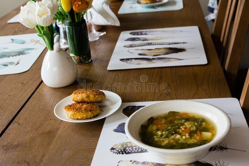 Duas costoletas e uma placa da sopa na tabela de jantar fotos de stock