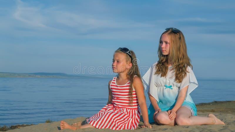 Duas crianças adolescentes estão sentando-se na praia imagem de stock