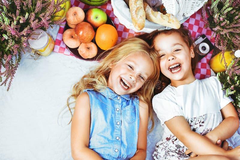 Duas crianças alegres que encontram-se em uma cobertura do piquenique entre rafrescamentos fotografia de stock royalty free