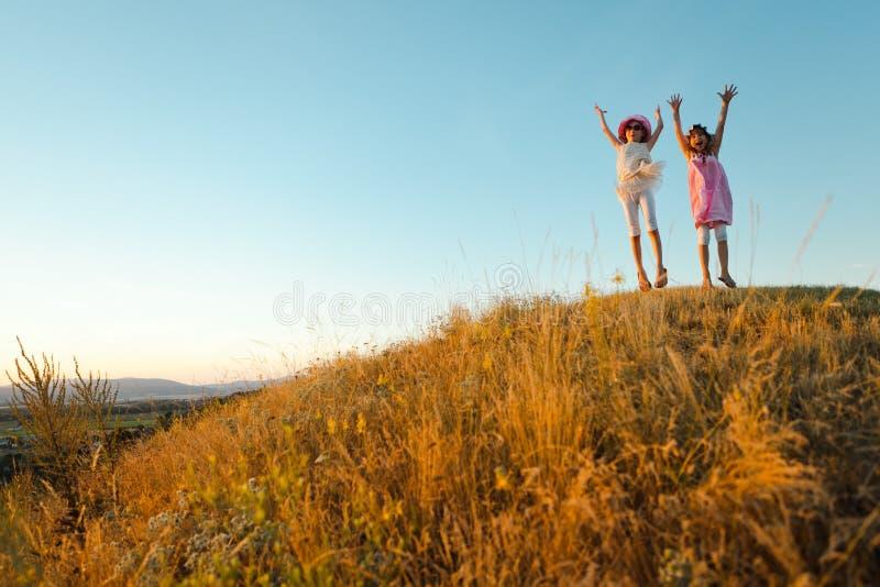 Duas crianças alegres saltaram e levantaram as mãos acima - do por do sol após o dia de verão fotos de stock royalty free
