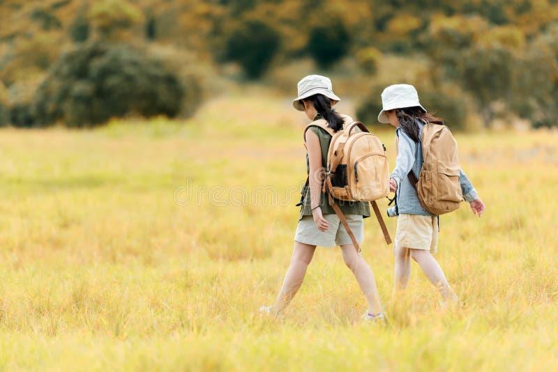 Duas crianças asiáticas do amigo que guardam o mapa e que andam com aventura e turismo para o destino e viagens do lazer para a e foto de stock