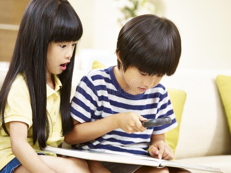 Duas crianças asiáticas que jogam com uma lente de aumento em casa fotografia de stock
