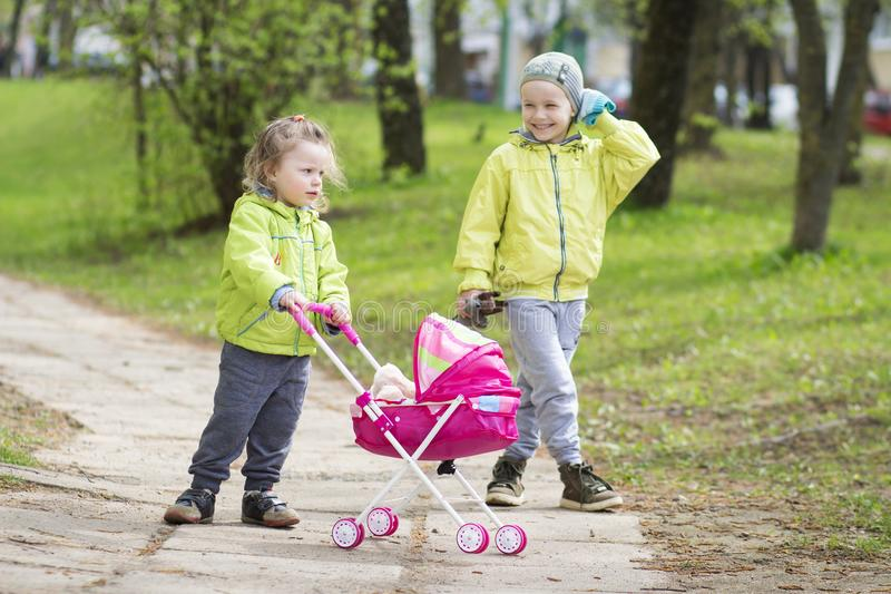 Duas crianças bebê e menino que jogam na jarda com um carrinho de criança do brinquedo fotografia de stock
