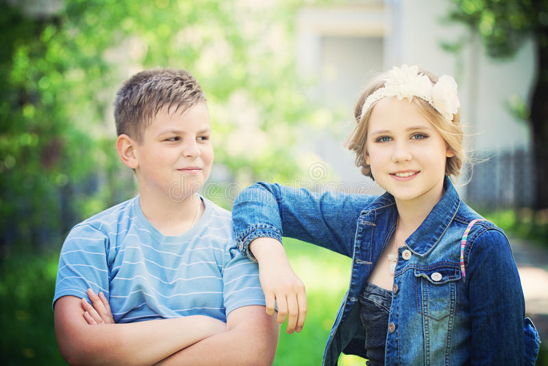Duas crianças bonitas exteriores O menino novo olha a menina imagens de stock