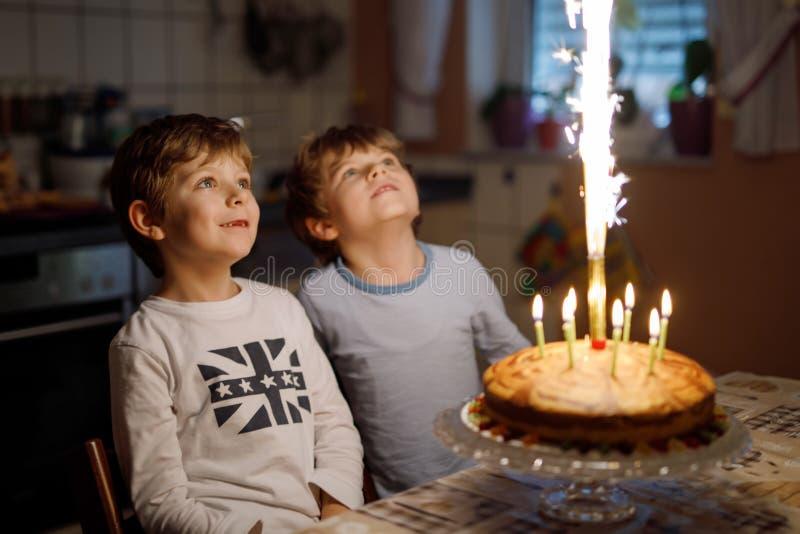 Duas crianças bonitas, meninos prées-escolar pequenos que comemoram o aniversário e que fundem velas imagens de stock royalty free