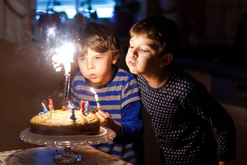 Duas crianças bonitas, meninos prées-escolar pequenos que comemoram o aniversário e que fundem velas foto de stock