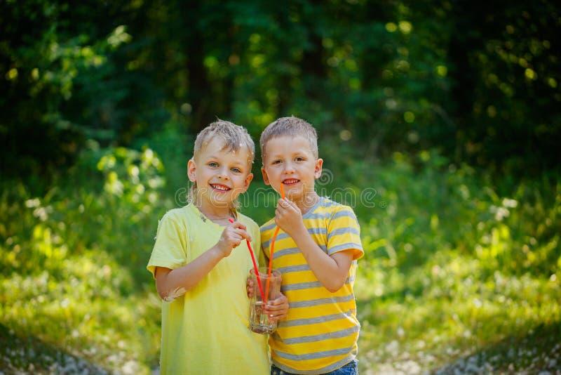 Duas crianças bonitos, amigos de menino, água potável no parque em l fotos de stock royalty free