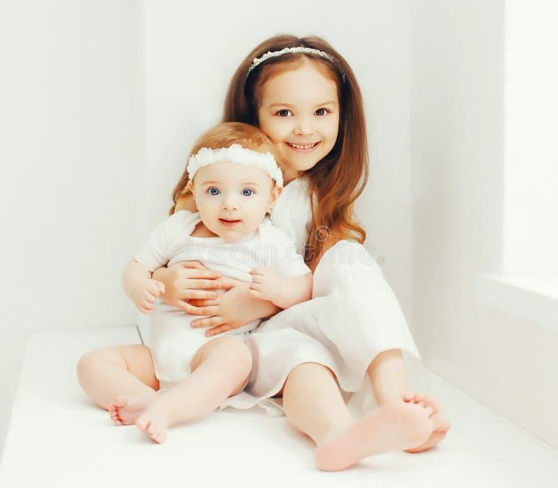 Duas crianças bonitos das irmãs junto em casa foto de stock