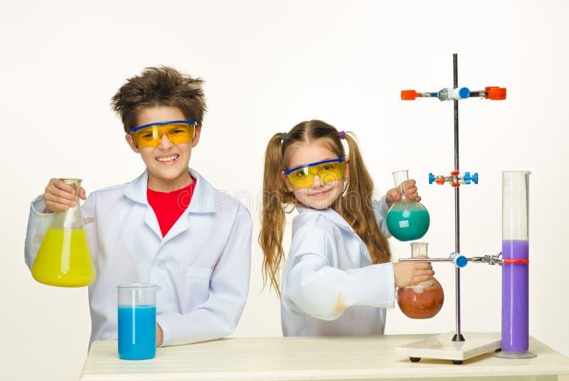 Duas crianças bonitos na fatura da lição da química imagens de stock royalty free
