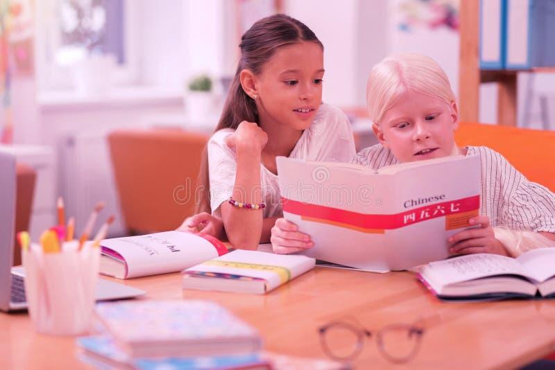 Duas crianças bonitos que leem um livro chinês foto de stock royalty free