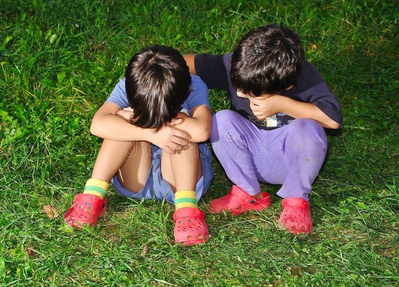 Duas crianças bonitos que sentam-se na terra foto de stock royalty free