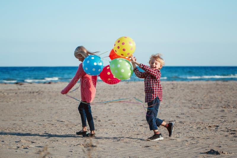 Duas crianças caucasianos brancas engraçadas caçoam com o grupo colorido dos balões, jogando a corrida na praia no por do sol, ve foto de stock