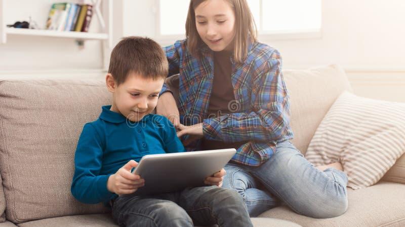 Duas crianças com o dispositivo no sofá em casa foto de stock royalty free