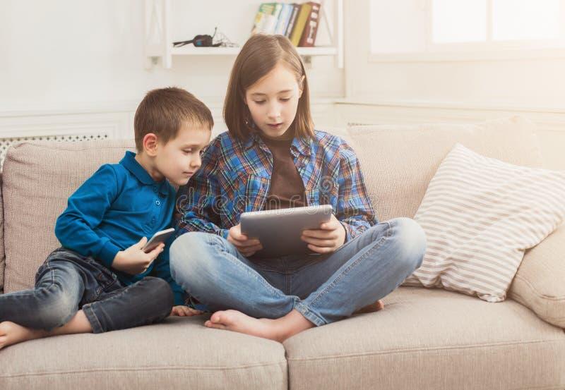 Duas crianças com os dispositivos no sofá em casa imagens de stock