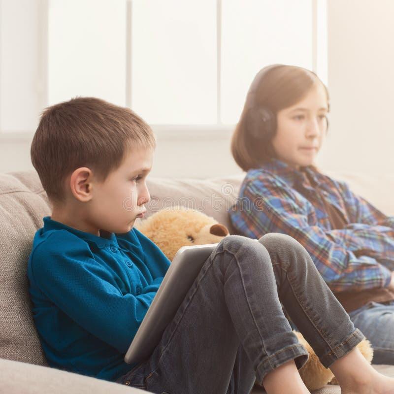 Duas crianças com os dispositivos no sofá em casa foto de stock