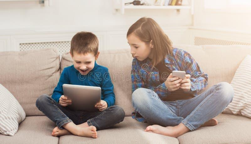 Duas crianças com os dispositivos no sofá em casa fotografia de stock royalty free