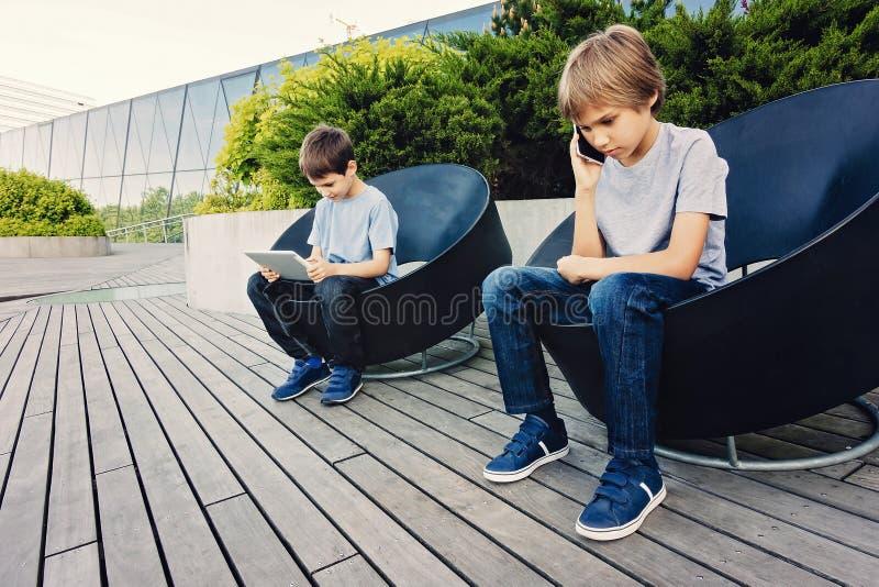 Duas crianças com tabuleta e o telefone esperto na cidade fora foto de stock
