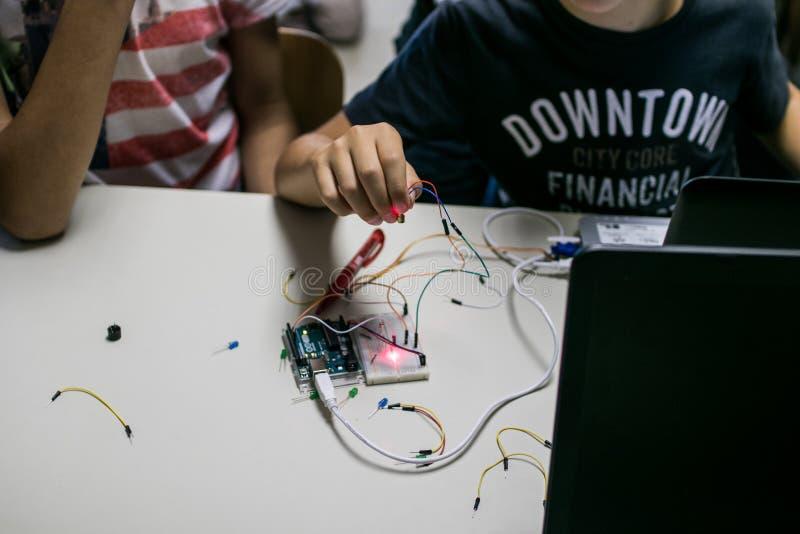 Duas crianças constroem um circuito do protótipo com um controle vermelho do laser fotos de stock