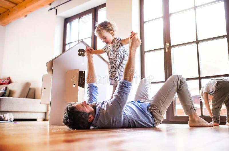 Duas crianças da criança com o pai que joga dentro em casa fotografia de stock royalty free