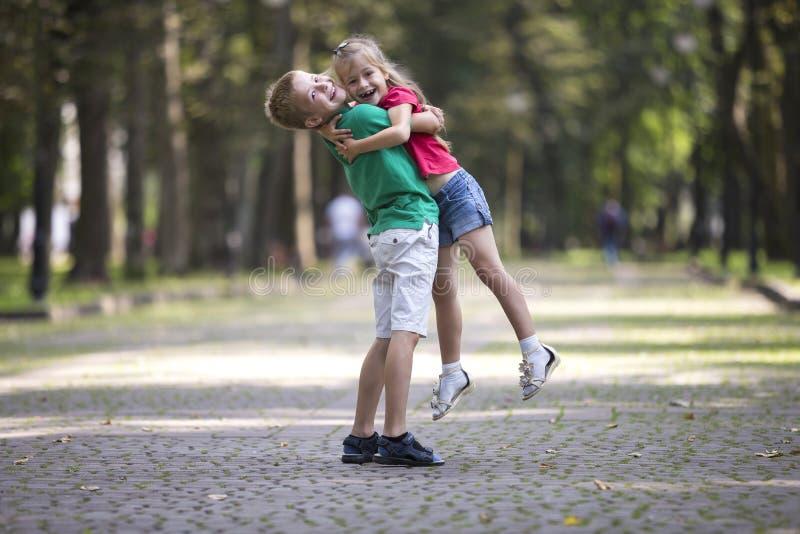 Duas crianças de sorriso engraçadas novas bonitos, menina e menino, irmã da terra arrendada do irmão em seus braços, tendo o dive fotografia de stock