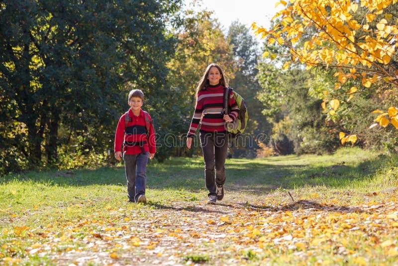 Duas crianças de sorriso no parque do outono com trouxas fotografia de stock