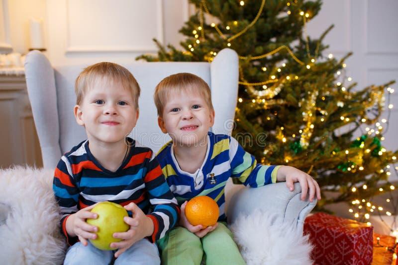 Duas crianças de sorriso pequenas, meninos mantêm frutos - maçã e laranja no fundo da árvore de Natal Crianças amigáveis felizes fotografia de stock royalty free
