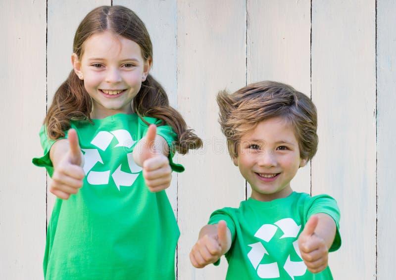 Duas crianças de sorriso que mostram os polegares acima fotografia de stock royalty free