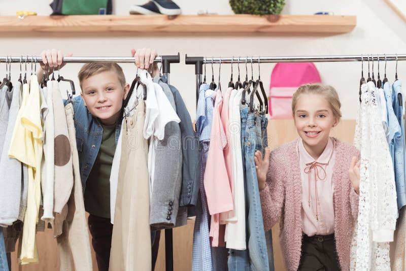 duas crianças de sorriso que olham a câmera ao estar sob o gancho de pano foto de stock