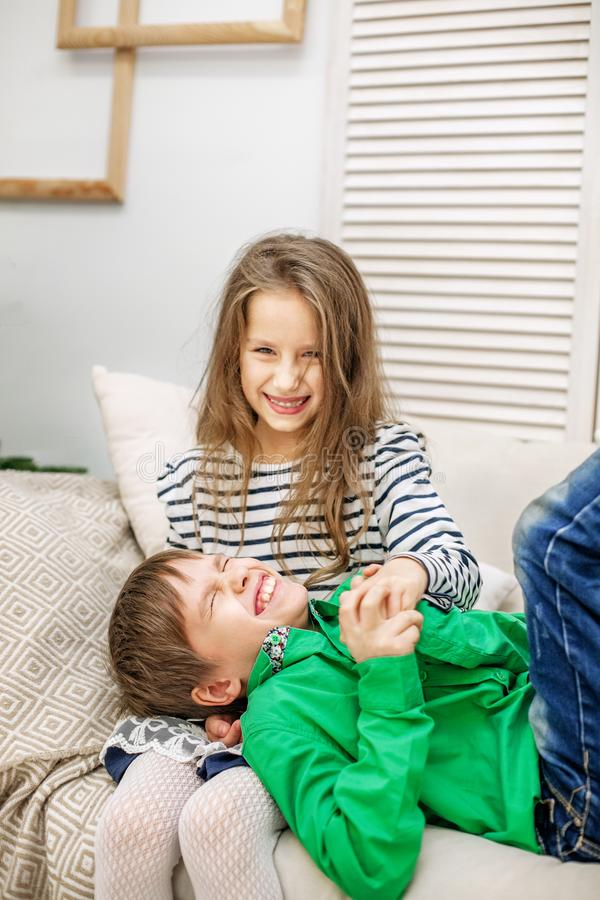 Duas crianças desenfreados no sofá O menino e a menina O engodo fotos de stock