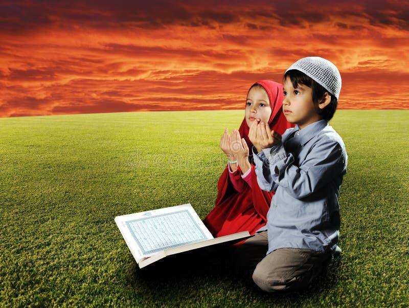 Duas crianças dos muçulmanos que sentam-se no prado fotografia de stock