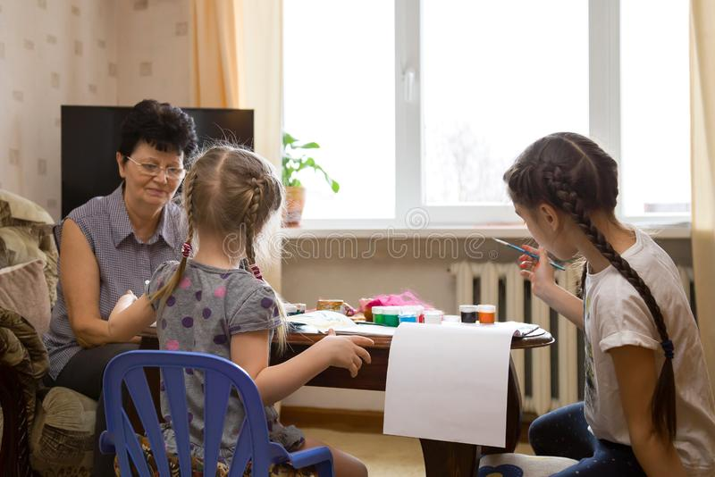 Duas crianças e avó que pintam em casa imagens de stock royalty free