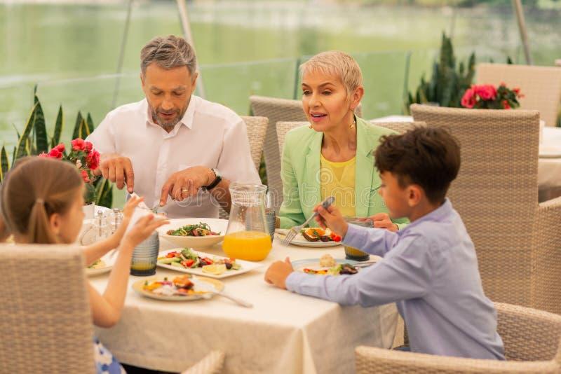 Duas crianças e avós que apreciam a manhã agradável no restaurante imagem de stock