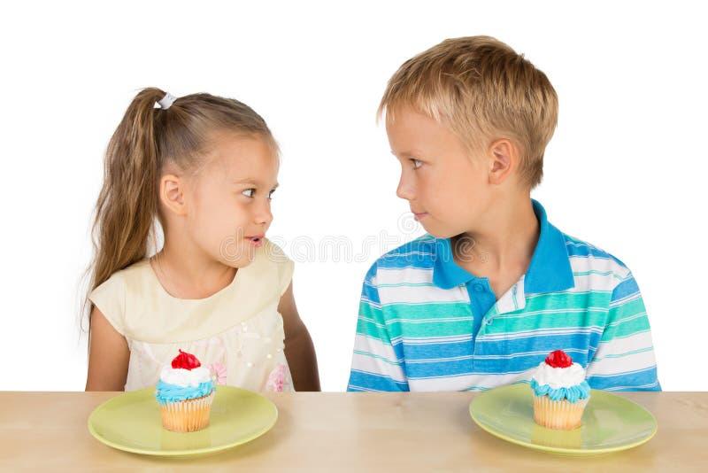 Duas crianças e dois queques fotografia de stock royalty free