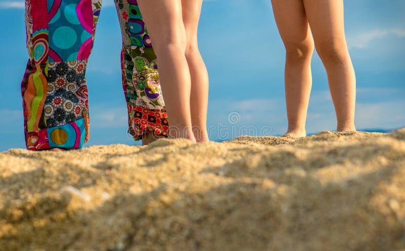 Duas crianças e mãe que jogam na praia imagens de stock