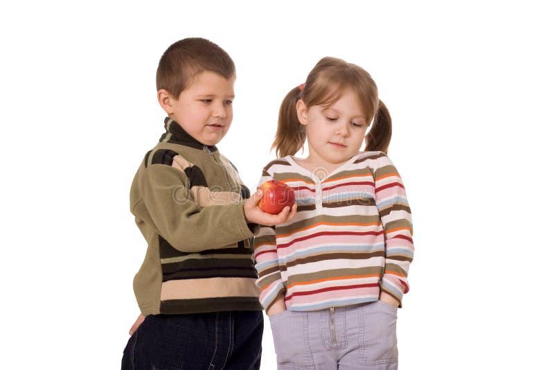 Duas crianças e uma maçã fotografia de stock