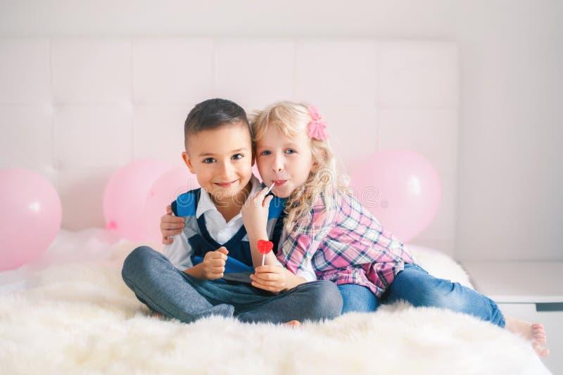 duas crianças engraçadas adoráveis bonitos caucasianos brancas felizes que comem pirulitos dados forma coração fotografia de stock royalty free